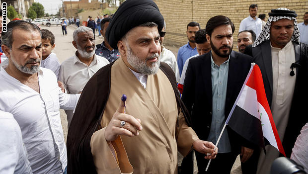Iraqi Shiite cleric and leader Moqtada al-Sadr (C-L) shows his ink-stained index finger and holds a national flag while surrounded by people outside a polling station in the central holy city of Najaf on May 12, 2018 as the country votes in the first parliamentary election since declaring victory over the Islamic State (IS) group. - Polling stations opened at 7:00 am for the roughly 24.5 million registered voters to cast their ballots across the conflict-scarred nation. (Photo by Haidar HAMDANI / AFP)        (Photo credit should read HAIDAR HAMDANI/AFP/Getty Images)